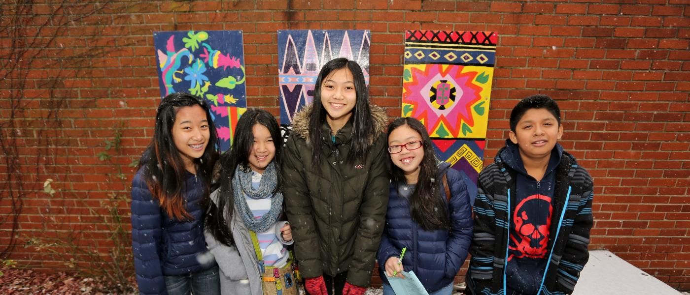 A group of students are standing in front of an outdoor mural.