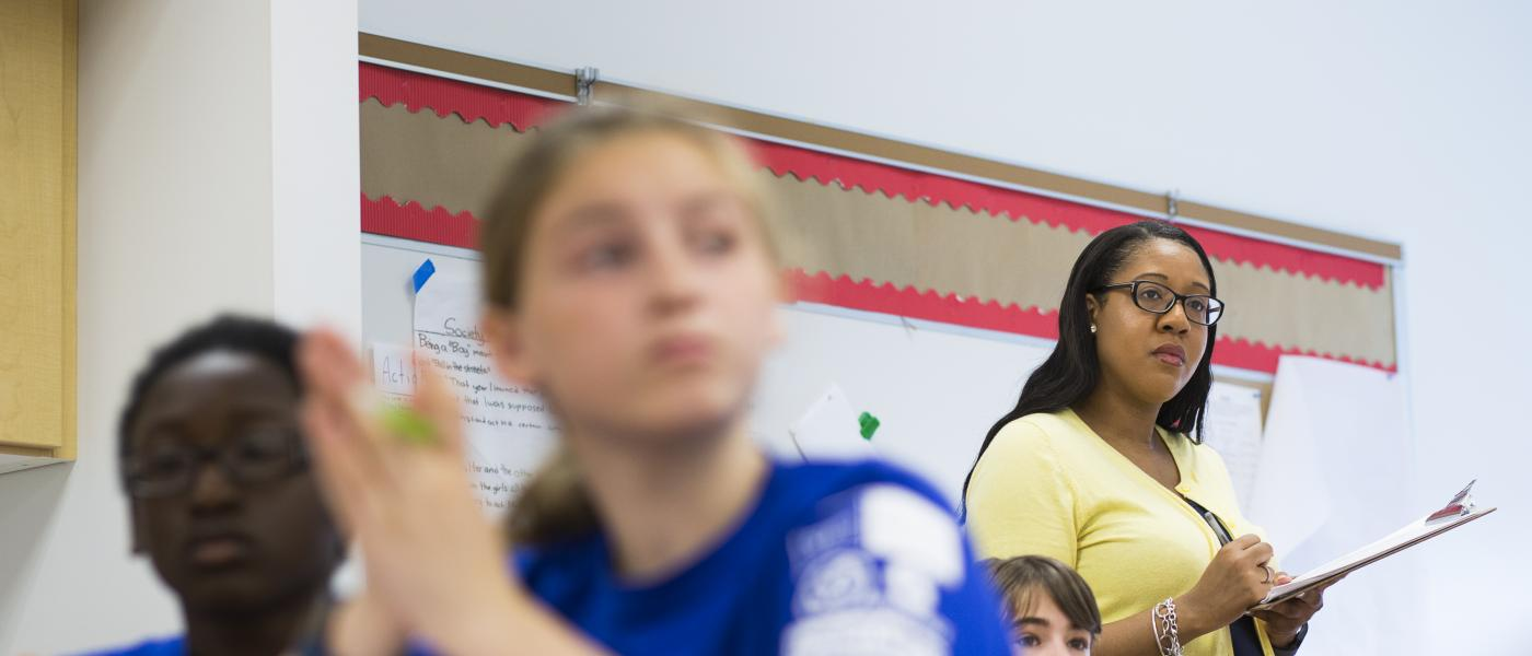 A teacher is standing in the classroom observing a student presentation.